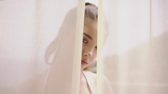 seductive woman hiding behind transparent curtain - seduction stock videos & royalty-free footage