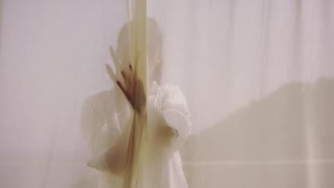 vídeos y material grabado en eventos de stock de mujer seductora escondida detrás de la cortina transparente - sombra