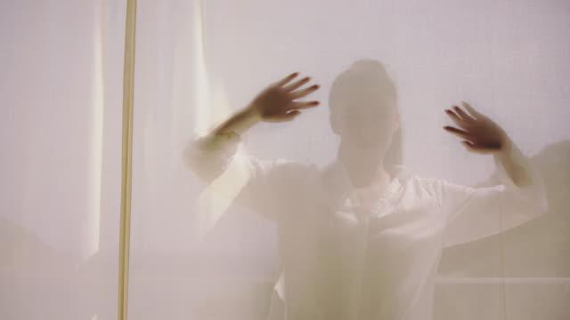 verführerische frau versteckt sich hinter transparentem vorhang - terrasse grundstück stock-videos und b-roll-filmmaterial