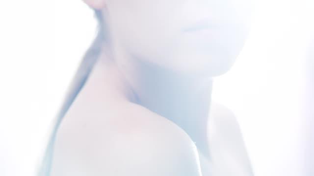 魅惑的な女性の唇がクローズアップ。フェイススキンケア。レンズフレア - 後ろで束ねた髪点の映像素材/bロール