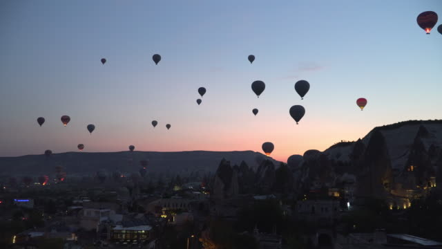 see hot air balloons start  flying before sunrise from city, cappadocia, turkey - air vehicle stock videos & royalty-free footage