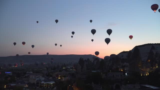 stockvideo's en b-roll-footage met zie hete lucht ballonnen beginnen vliegen voor zonsopgang vanuit stad, cappadocië, turkije - air vehicle