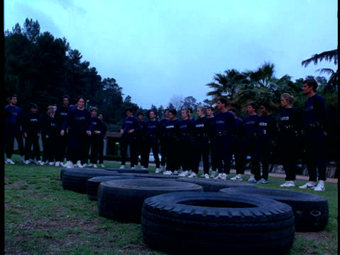 see police officers in training uniforms /  police force training / running through tires on ground / recruits on exercise field