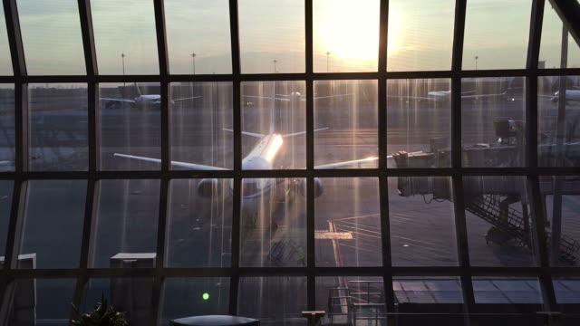 vídeos de stock, filmes e b-roll de ver através da janela de vidro na porta do ar - área de embarque de aeroporto