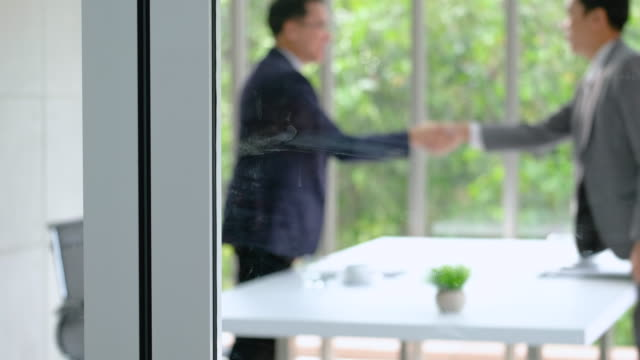 see through meeting room window.blur of two asian businessman sign contract and handshake each other with business deal.partnership concept. - press conference stock videos and b-roll footage