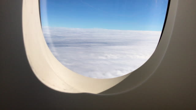 see through window seat in airplane to cloudy and blue sky when flying. - passenger cabin stock videos & royalty-free footage
