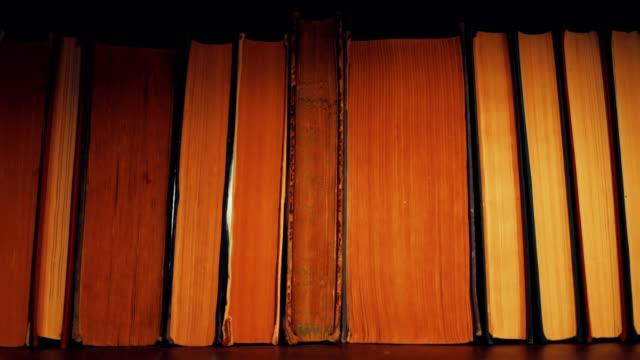 懐中電灯で本を求めてください。 - 本棚点の映像素材/bロール