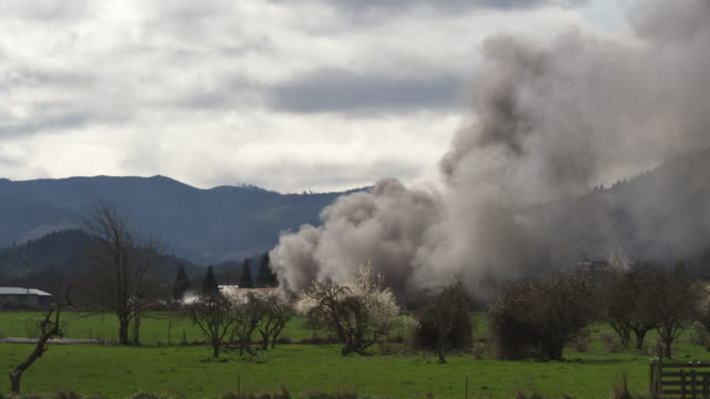 seen from across a rural field, smoke billows from a burning house - myrtle creek stock videos & royalty-free footage
