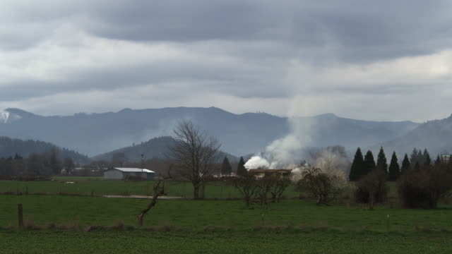 seen from across a rural field, smoke rises from a burning house - myrtle creek stock videos & royalty-free footage