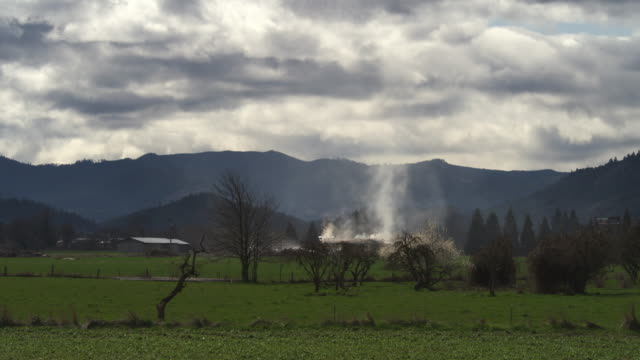 seen from across a rural field, smoke rises from the roof of a house on fire - myrtle creek stock videos & royalty-free footage