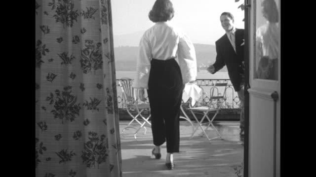 seen through curtained open doors a young man watches as a waiter sets a table he's then joined by woman in slacks with blouse of full sleeves and he... - blouse stock videos & royalty-free footage