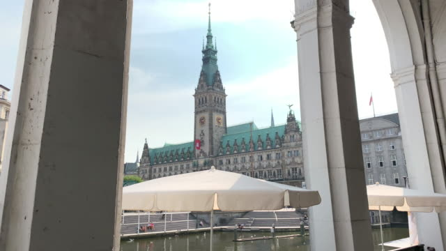 seen through the colonnades of the alster arcade, the hamburg town hall (rathaus), the seat of the state parliament - rathaus hamburg stock-videos und b-roll-filmmaterial