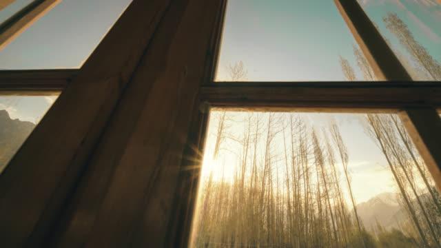 durch das fenster gesehen, bei sonnenaufgang - wohngebäude innenansicht stock-videos und b-roll-filmmaterial