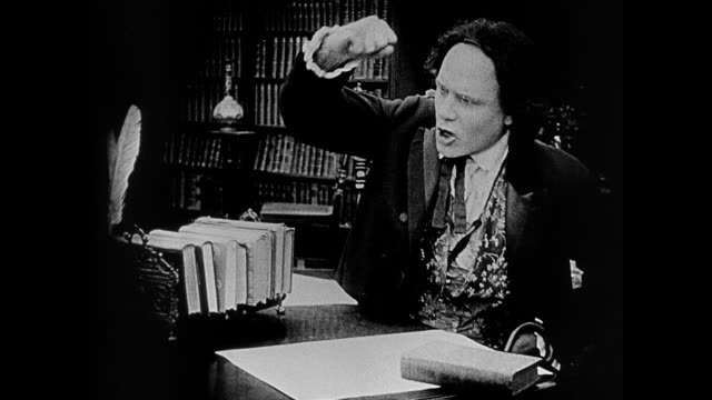 stockvideo's en b-roll-footage met 1860s in the middle of a serious discussion, a man (ralph lewis) adjusts his wig and rubs his head - pruik