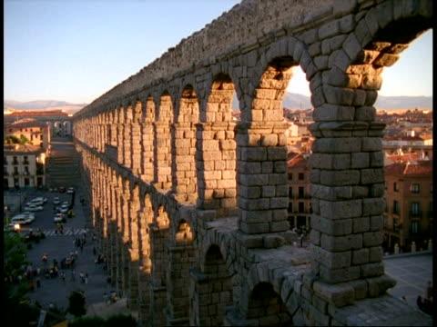 segouia city, spain - sun shining through side angled view of large high roman aqueduct towering above city street - 見渡す点の映像素材/bロール