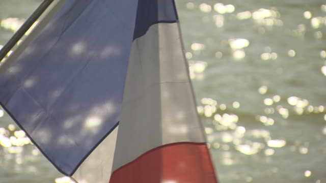 French flag with the sun shining through the back of it camera pans to the sun glistening on the water flag fades out