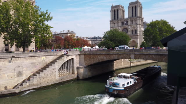 ws seine river with tourboats and notre dame de paris cathedral, paris, france - river seine stock videos & royalty-free footage