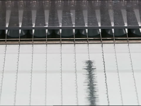 vídeos de stock, filmes e b-roll de cu seismogram printing seismic graph lines - papel quadriculado