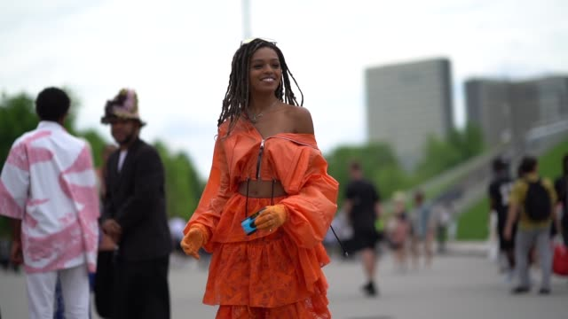 selah marley wears an orange off-shoulder ruflfled lace mesh bare belly dress, necklace, gloves, white leggings, heels shoes outside kenzo, during... - fashion week stock videos & royalty-free footage
