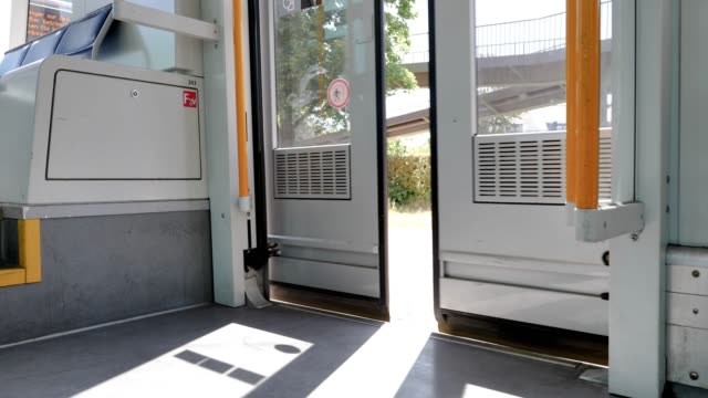 selected focus view at opening and closing automatic doors of light rail tram which stop at metro light rail station in düsseldorf, germany. - tram stock-videos und b-roll-filmmaterial