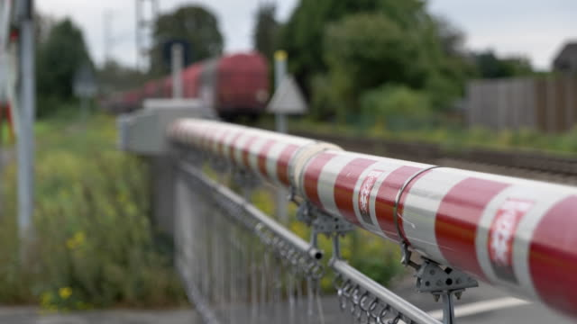 selected focus view at red and white level crossing railway barrier which block the road until it was lifted, and locomotive move on the rail on countryside in germany. - level crossing stock videos & royalty-free footage