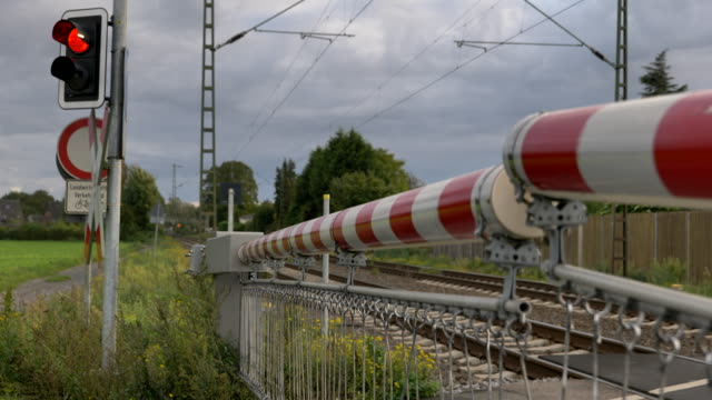 selected focus view at red and white level crossing railway barrier which block the road until it was lifted, and locomotive move on the rail on countryside in germany. - germany stock videos & royalty-free footage