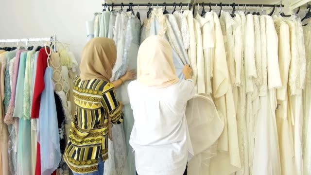 vídeos de stock, filmes e b-roll de selecionando através de uma coleção de casamento em um local bridal boutique - vestuário modesto