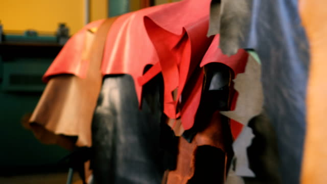 selection of leather goods hanging in workshop - leather stock videos and b-roll footage