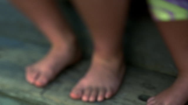 selective focus close up pan bare feet of two children next to lap of person sitting on steps /nova scotia - poor family stock videos & royalty-free footage