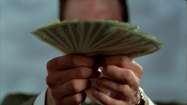 selective focus close up tilt down man offering fanned stack of $100 bills - giving stock videos & royalty-free footage