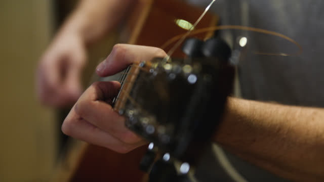 selective focus down the neck of an acoustic guitar as chords are played - guitar stock videos & royalty-free footage