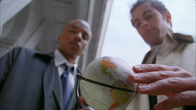 Selective focus low angle close up businessman spinning small globe / Black businessman stopping it with finger