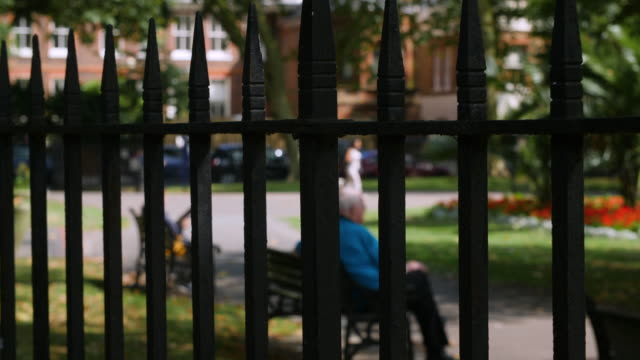 selective focus man sitting on park bench seen through fence bars - public park stock videos & royalty-free footage