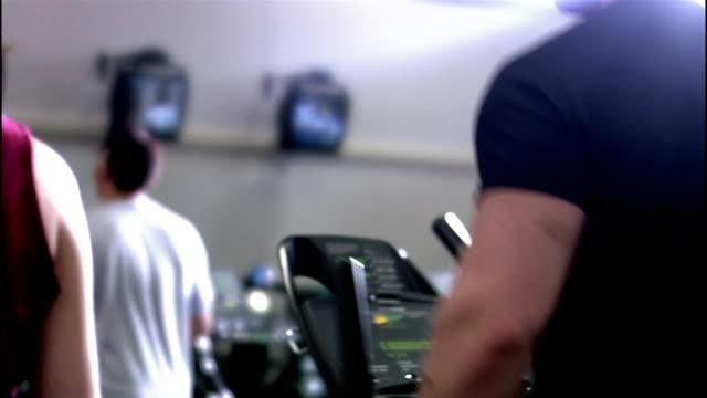 selective focus medium shot dolly shot men and women using elliptical trainers at gym - ウィスコンシン州アップルトン点の映像素材/bロール