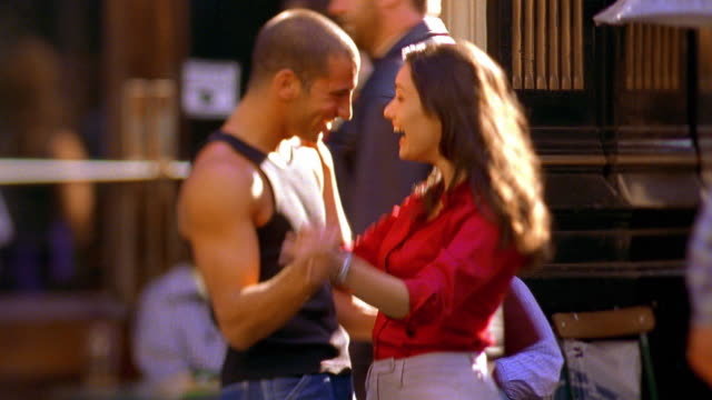 vidéos et rushes de selective focus medium shot man with muscles in tank top dancing with woman on city sidewalk / london - cadrage aux genoux