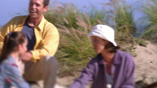 selective focus medium shot pan family sitting on beach and having picnic / california - ギフトバスケット点の映像素材/bロール