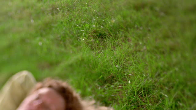 stockvideo's en b-roll-footage met selective focus medium shot pan middle aged woman lying on grass with eyes closed / nova scotia, canada - roodhoofd