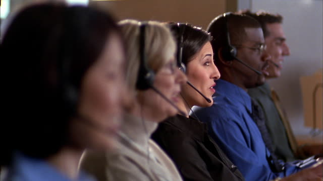 selective focus medium shot row of telemarketers at work - call centre stock videos & royalty-free footage