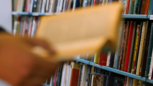 selective focus of a man turning pages of a paperback book in front of a bookshelf - bookstore stock videos & royalty-free footage