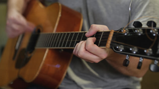 Selective focus of chords being strummed on an acoustic guitar