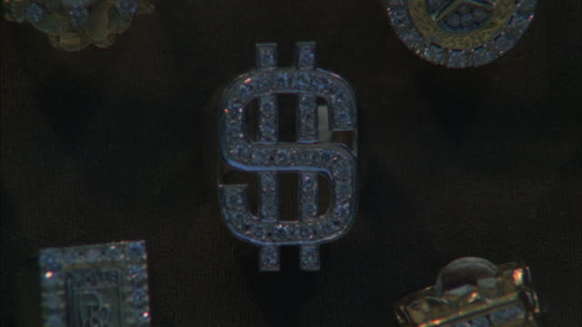Selective focus of diamond-encrusted dollar-sign ring.