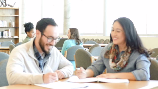 selective focus of two hispanic mid adult students studying together in college libarary - mature student stock videos & royalty-free footage