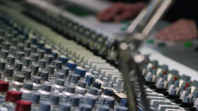 vidéos et rushes de selective focus on the dials of a large sound mixing desk - matériel d'enregistrement