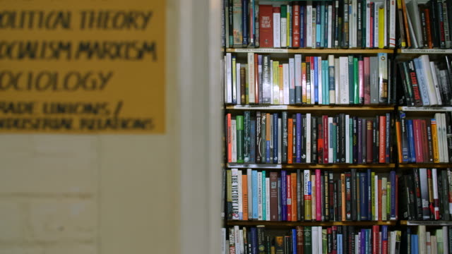 selective focus shot of a bookshelf filled with political theory books - book shop stock videos & royalty-free footage