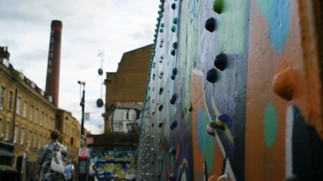 selective focus shot of a colourful wall on brick lane with truman brewery chimney looming in the background - poster stock videos & royalty-free footage