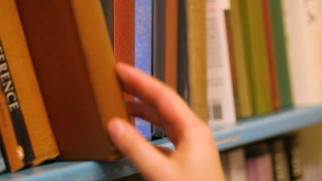 vídeos de stock, filmes e b-roll de selective focus shot of a female browsing through hardback books on a bookshelf - livraria