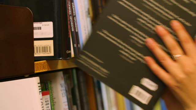 selective focus shot of a female selecting and replacing paperback books off a bookshelf - bookstore stock videos & royalty-free footage