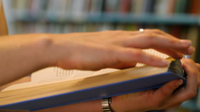 selective focus shot of a female turning pages of a blue hardback book - bookstore stock videos & royalty-free footage