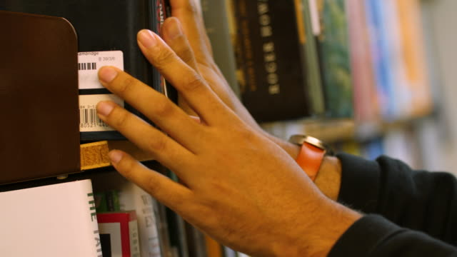 selective focus shot of a male browsing through hardback books on a bookshelf - book shop stock videos & royalty-free footage