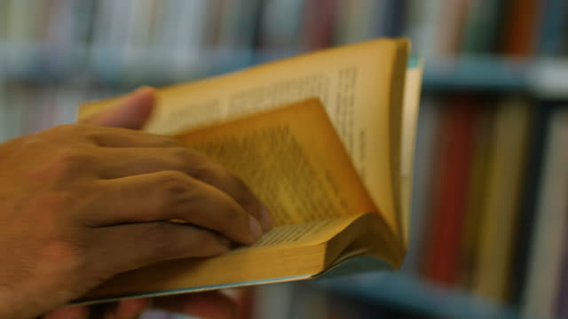 selective focus shot of a male turning pages of a paperback book - wisdom stock videos & royalty-free footage